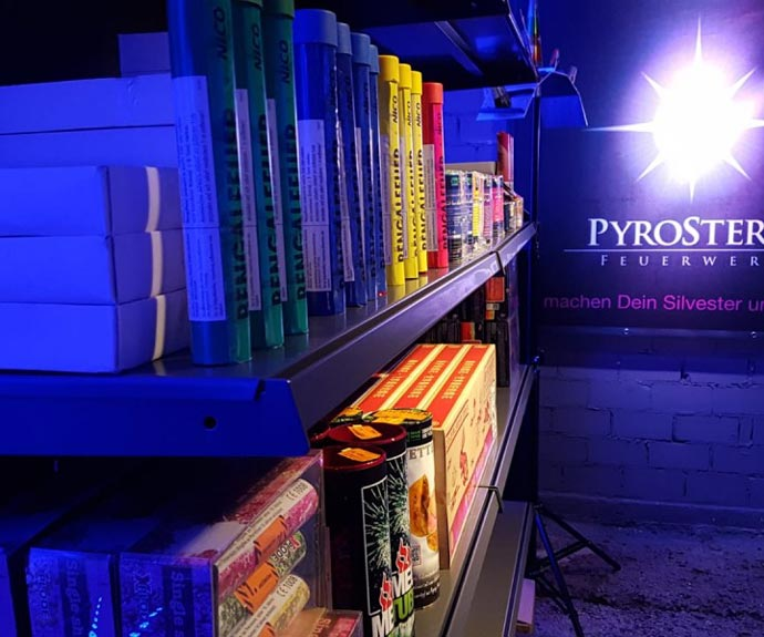 Ein Bild das in einem Feuerwerkfsverkauf ein Regal voller Feuerwerksartikel zeigt