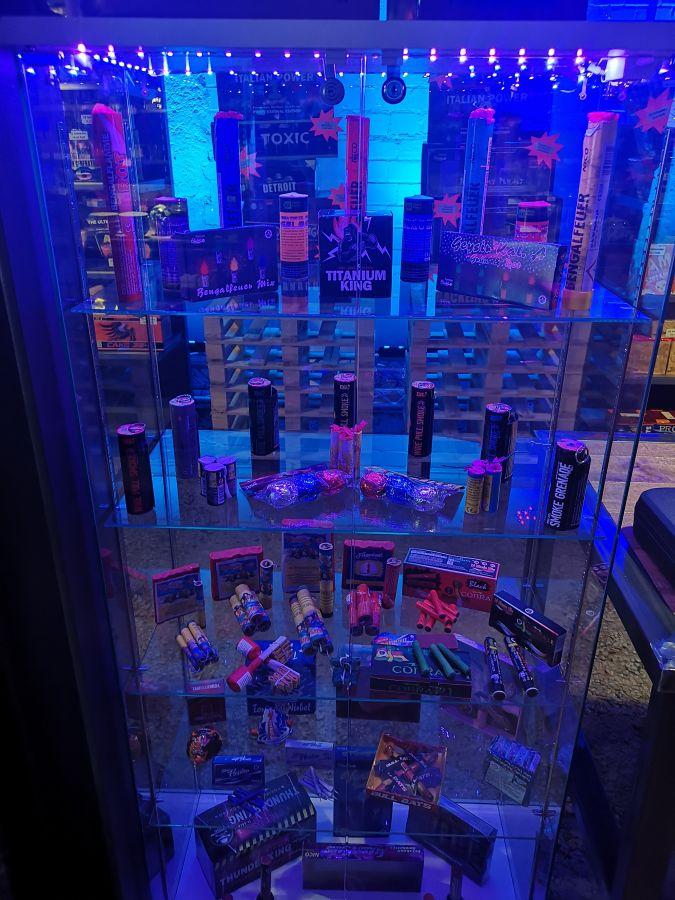 Ein Bild das viele Feuerwerksartikel in einer Feuerwerksvitrine zeigt